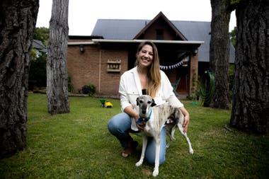 Bella y uno de sus perros en el patio de su casa
